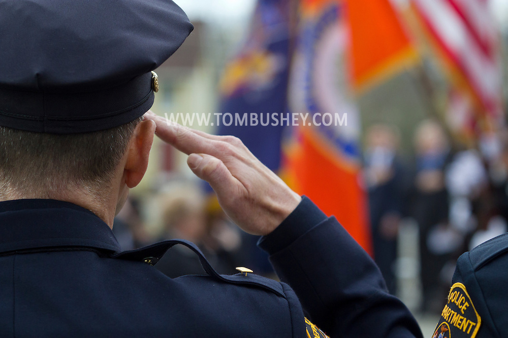 Goshen, New York - A police officer salutes during the Orange County Law Enforcement Officer Memorial Service on May 2, 2014. The memorial service honors the memory of the 27 members of the Orange County law enforcement community that died in the line of duty. The service also pays tribute the families and loved ones left behind for their courage, dignity and perseverance.