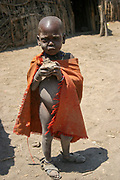 Young Maasai child at the entrance to a hut. Maasai is an ethnic group of semi-nomadic people Photographed in Kenya