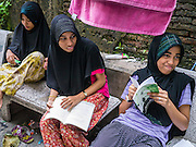 20 APRIL 2013 - BANGKOK, THAILAND:   Muslim schoolgirls do their homework in the Haroon neighborhood in Bangkok. It is a relatively small Muslim enclave originally settled by traders from the Dutch East Indies, what is now Indonesia. PHOTO BY JACK KURTZ