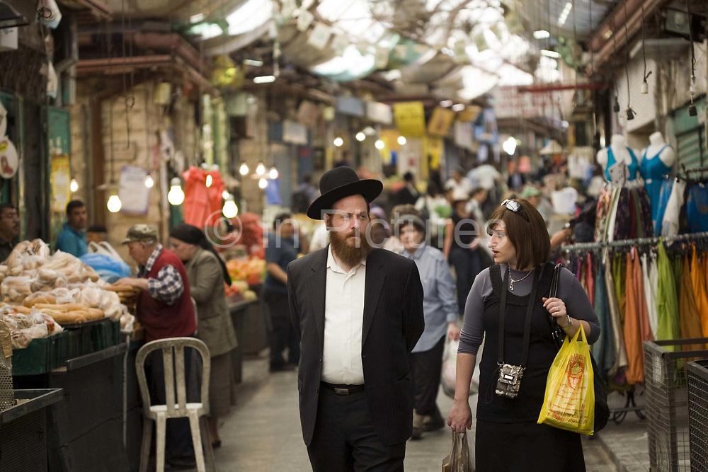 An Orthodox Jewish man and his wife shopping in the Mahane Yahuda Market, Jerusalem, Israel