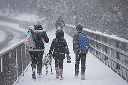 © Licensed to London News Pictures. 27/02/2018. New Hythe, UK.  A family cross a bridge over the M20 as snow falls. Freezing temperatures and heavy snow are affecting large parts of Kent.  Photo credit: Peter Macdiarmid/LNP