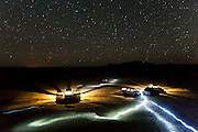 Vehicles and headlamps shine brightly under a starry night sky at a campsite near Hanksville, Utah.