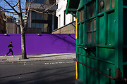 A lone woman jogger runs past purple construction hoarding and a green taxi drivers' shelter. The runner exercises on a bright afternoon in a side street in Temple Place, close to Waterloo bridge. The garish purple stripe of colour contrasts the green foreground belonging to the Victorian structure. Because cab drivers weren't allowed to leave their vehicles when parked at a stand, it was difficult for them to get a hot meal while at work, so The Earl of Shaftesbury (God bless 'im) and a few philanthropic chums decided to create a cabbie's charity in 1874. Between 1875 and 1914, a total of 61 shelters were built at cost of around £200 each. Because the shelters stood on a public highway, the police stipulated that they weren't allowed to be any larger than a horse and cart.