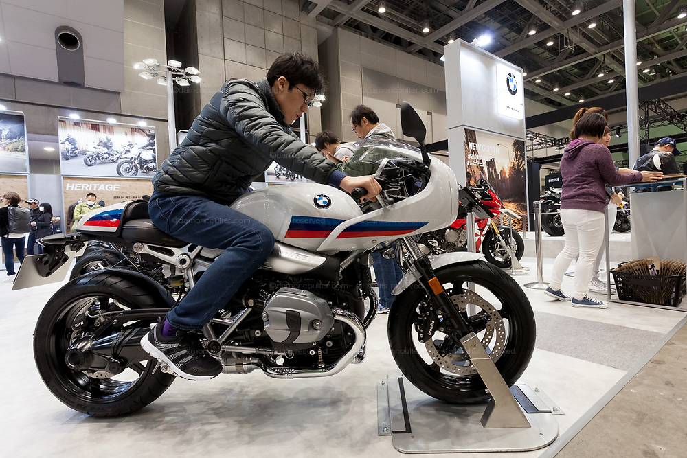 A Japanese man tries out sitting on a new BMW motorbike at the 44th annual Tokyo Motorcycle show. Tokyo Big Sight exhibition hall, Odaiba, Tokyo, Japan. Friday March 24th 2017. The show runs from Friday March 24th to Sunday March 26th and showcases technological innovations from all the main motorcycle manufacturers along with companies providing protective helmets pads and  clothing to decoration and even camping gear for bike-touring..