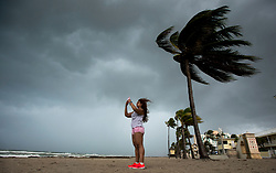 A woman takes a souvenir photograph along the beach with blowing winds and threatening skies in anticipation for Hurricane Irma, in Hollywood, Fla., Saturday, September 9, 2017. THE CANADIAN PRESS/Paul Chiasson