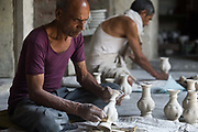 A potter finishing a clay pot at a factory in Sanganer, Jaipur, India