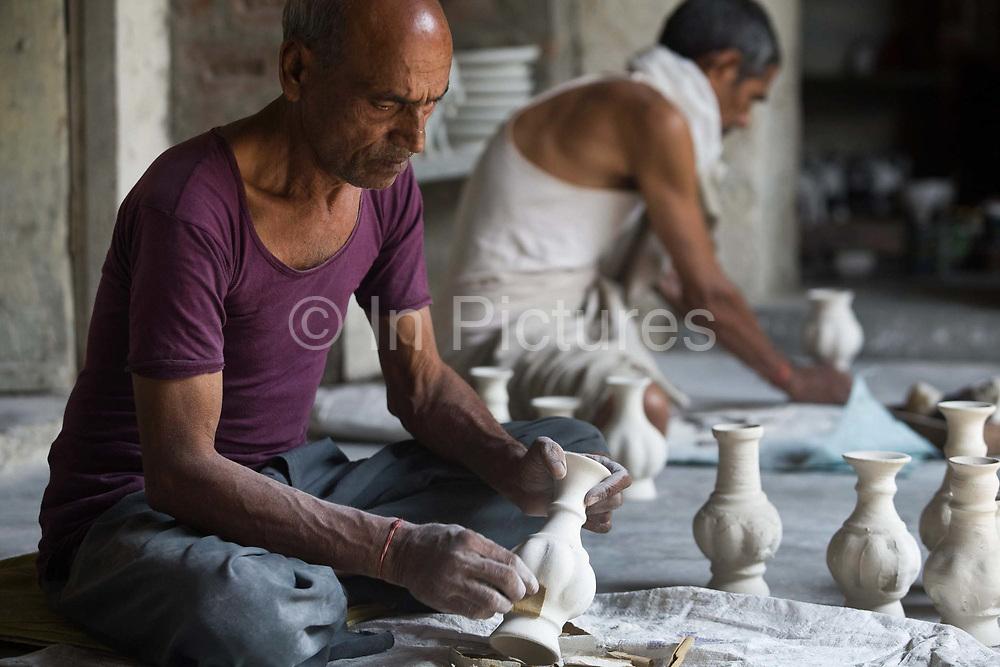 A potter finishing a clay pot at a factory in Sanganer, Jaipur, India