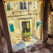 A home and front door in the old city of Dubrovnik, Croatia, framed by a window of the city's outer protective wall. <br />