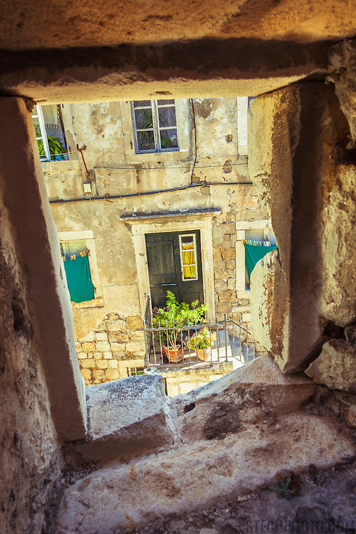 """A home and front door in the old city of Dubrovnik, Croatia, framed by a window of the city's outer protective wall. <br /> <br /> Dubrovnik serves as the official setting of """"King's Landing"""" from the popular TV show """"Game of Thrones"""".<br /> <br /> LICENSING: This image can be licensed through SpacesImages. Click on the link below:<br /> <br /> http://tinyurl.com/czrrf2c"""