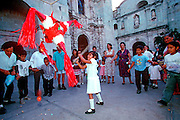 MEXICO, FESTIVALS Oaxaca, traditional Christmas Posadas with children breaking a pinata full of candy and fruit in front of local church