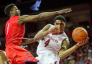 Nov 18, 2013; Fayetteville, AR, USA; Arkansas Razorback guard Coty Clarke (4) makes a pass around Southern Methodist Mustang guard Ryan Manuel (1) during the first half of a game at Bud Walton Arena. Mandatory Credit: Beth Hall-USA TODAY Sports