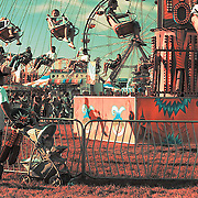A man wearing a white t-shirt standing nest to a baby stroller watches a swing ride at the Western Idaho Fair
