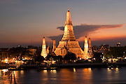 """07 MARCH 2009 -- BANGKOK, THAILAND: Sunset at Wat Arun, a Buddhist temple (wat) in the Bangkok Yai district of Bangkok, Thailand, on the west bank of the Chao Phraya River. The full name of the temple is Wat Arunratchawararam Ratchaworamahavihara. The outstanding feature of Wat Arun is its central prang (Khmer-style tower). It may be named """"Temple of the Dawn"""" because the first light of morning reflects off the surface of the temple with a pearly iridescence. Steep steps lead to the two terraces. The height is reported by different sources as between 66,80 m and 86 m. The corners are surrounded by 4 smaller satellite prangs. The prangs are decorated by seashells and bits of porcelain which had previously been used as ballast by boats coming to Bangkok from China. The central prang is topped with a seven-pronged trident, referred to by many sources as the """"trident of Shiva"""". Around the base of the prangs are various figures of ancient Chinese soldiers and animals. Over the second terrace are four statues of the Hindu god Indra riding on Erawan. The temple was built in the days of Thailand's ancient capital of Ayutthaya and originally known as Wat Makok (The Olive Temple). In the ensuing era when Thonburi was capital, King Taksin changed the name to Wat Chaeng. The later King Rama II. changed the name to Wat Arunratchatharam. He restored the temple and enlarged the central prang. The work was finished by King Rama III. King Rama IV gave the temple the present name Wat Arunratchawararam. As a sign of changing times, Wat Arun officially ordained its first westerner, an American, in 2005. The central prang symbolizes Mount Meru of the Indian cosmology. The satellite prangs are devoted to the wind god Phra Phai. Photo By Jack Kurtz"""