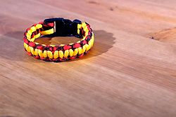 26 August 2015:   Studio - a cobra braid survival bracelet in red, black, and yellow with a plastic clasp created from paracord 550