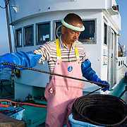 Hasegawa-san concentrating on bringing hundreds of meters of line back onto his fishing boat in an organized manner. The line was attached to traps set for catching crabs at 700m to 1000m depth in Suruga Bay, Japan.