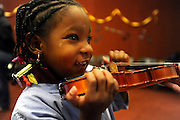 Andy Woods Elementary pre-schooler Amari Williams,4, is delighted as she tries a violin with her own hands at the Tyler Public Library. Preschoolers were exposed to classical music which will be played by the East Texas Symphony Orchestra on Saturday. Photo: Jaime R. Carrero/Tyler Morning Telegraph