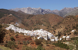 View of Tolox; Andalucia; with white painted houses and mountains in background,