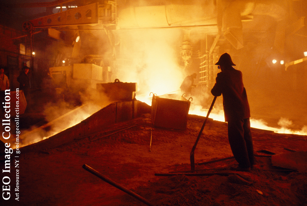 Industrial view of workers at the blast furnace at a steel plant.
