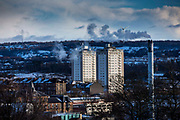 Two blocks of flats, a smoking chimney and a wind turbine on Glasgow South side taken from Queens Park, Glasgow.