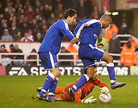 Photo: Daniel Hambury.<br />Arsenal v Cardiff City. The FA Cup. 07/01/2006.<br />Arsenal's Manuel Almunia gets a hand to the ball as Cardiff's Jeff Whitley (R) and Alan Lee try to score a second Cardiff goal.