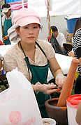Hmong cook preparing food for grinding in mortar and pestle in busy restaurant. Hmong Sports Festival St Paul Minnesota USA