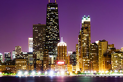Photo of Chicago at night with John Hancock Center building and other popular downtown Chicago city buildings. The John Hancock Center is one of the world's tallest skyscrapers and is a famous fixture in the Chicago skyline. Photo is high resolution and was taken in 2012.