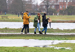 © Licensed to London News Pictures. 30/01/2021. London, UK. Walkers brave the wind, rain and flooding on Wimbledon Common in South West London this morning as the Met Office issue weather warnings for rain and flooding for large parts of England. The Met office has issued weather warnings for much of the UK this weekend for snow, torrential rain and flooding with disruption to travel as the stormy weather continues. Photo credit: Alex Lentati/LNP<br /> <br /> *Permission Granted*
