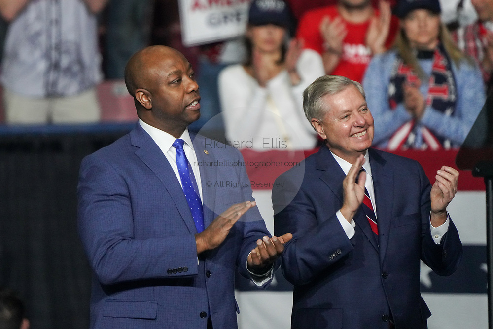 U.S. Senator Tim Scott, left, and Senator Lindsey Graham of South Carolina applaud during the Keep America Great Rally at the in the North Charleston Coliseum February 28 2020 in North Charleston, South Carolina.