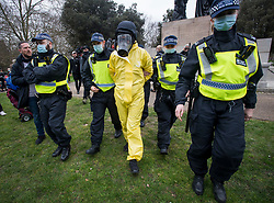 © Licensed to London News Pictures. 20/03/2021. London, UK. A man in a mock hazmat suit is detained by police  officers during a Rally for Freedom in central London, to protest against the continued lockdown restrictions imposed to fight the spread of coronavirus. Similar events are taking place at cities around the world. Photo credit: Ben Cawthra/LNP