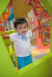 United States, Washington, Bellevue, KidsQuest Children's Museum, toddler peeking through curtains of birdhouse in Backyard exhibit