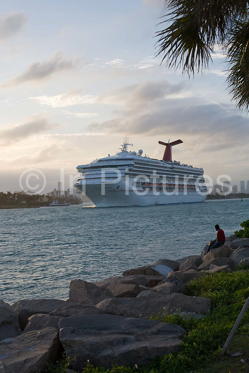 The cruise ship Carnival destiny leaving the port of Miami at South Pointe. South Pointe Park is a good place to watch cruise ships and cargo ships as they come and go through the channel in Biscayne Bay
