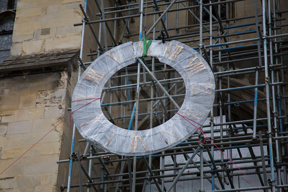 @Licensed to London News Pictures 27/11/2018.Canterbury, Kent. Canterbury clock face is hoisted over the edge of the parapet of Canterbury Cathedral. The Cathedral Clock and clock face built in 1855  and housed on the south west tower of Canterbury Cathedral is being dismantled ready to be renovated and re-guilded. The clock face weighing 78 kilos and measuring 8 feet in diameter is being shipped to the Cumbrai Clock Company in Penrith and will be absent from the cathedral for 18 months. Photo credit: Manu Palomeque/LNP