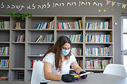 Schooling under COVID-19 Librarian with protective mask in an empty library at a Primary school. The outbreak of COVID-19 has forced governments around the world to impose a civil quarantine. The outcome of this is limited contact between people including students and teachers and minimal social interaction. Photographed at Kedem Primary School, Israel