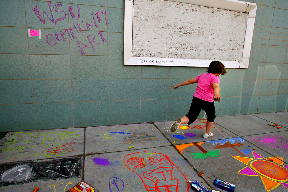 """A young girl skips through Washington State University Tri-Cities' community art section during Richland's annual Chalk Art Festival. Student Daniel Anderson described it as """"Dialogical Art"""" -- art that is created through the interactions and dialogue created by bringing people together. They encouraged any passersby to add to the piece and discouraged people from walking around it, saying that footsteps and smearing was as much a part of the process."""
