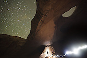 Ethan Welty stands at night below the central buttress of Wild Horse Window, San Rafael Swell, Utah.
