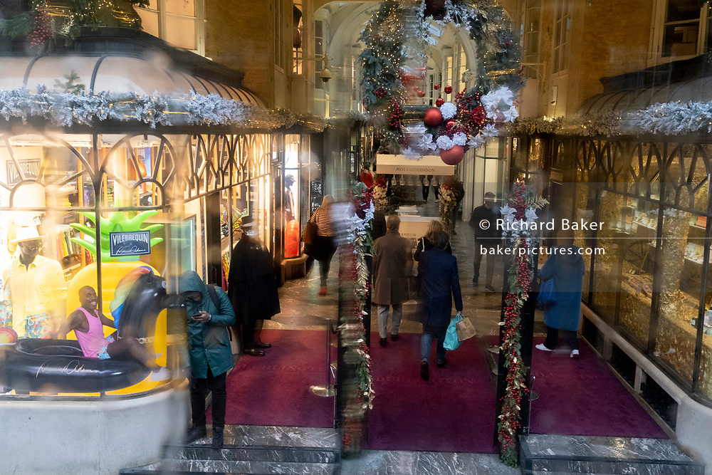 As the government announces the move from Tier 2 to Tier 3 before Christmas, shoppers pass beneath seasonal decorations in Quadrant Arcade on Regent Street during the second wave of the Coronavirus pandemic, on 14th December 2020, in London, England.