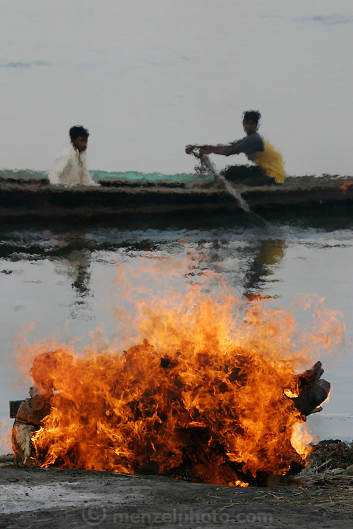 A rowboat passes, distorted by the heat waves rising from a body burning at the Harishchandra cremation grounds on the Ganges River in Varanasi, India. Just up river a man dries the clothes he just washed in the Ganges in the heat of a burning funeral pyre. The Harishchandra Ghat (also known as the Harish Chandra Ghat) is the smaller and more ancient of the two primary cremation grounds in Varanasi, on the banks of the Ganges River.