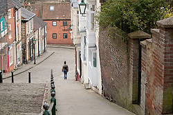 © Licensed to London News Pictures. 17/03/2020. Lincoln, Lincolnshire, UK. Deserted Lincoln. Pictured a lone person walking down Steep Hill. The streets leading from the top of the City (Bailgate) down to the railway station at the bottom of the City are usually filled with commuters on their way to work unlike this morning as the streets were eerily quiet. Photo credit: Dave Warren / LNP