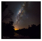 The Milky Way and Rio Cristalino (southern Amazon, Brazil). A mosaic of two images. The orange glow is the lights from the city of Alta Floresta. Mars and Saturn together with the orange star Antares form the triangle just to the right (north) of the galactic centre. Nikon D810, 14-24mm @ 14mm, f3.5, 10 sec, ISO3200, Manual modus