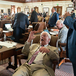 Rep. Charlie Geren, R-Fort Worth, reacts as lawmakers crack up Tuesday morning as the fake snake incident hits the desk of Rep. tracy King while Rep. Jeff Leach (on the floor) films.