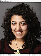 Portait of a high school senior in front of a grey background.