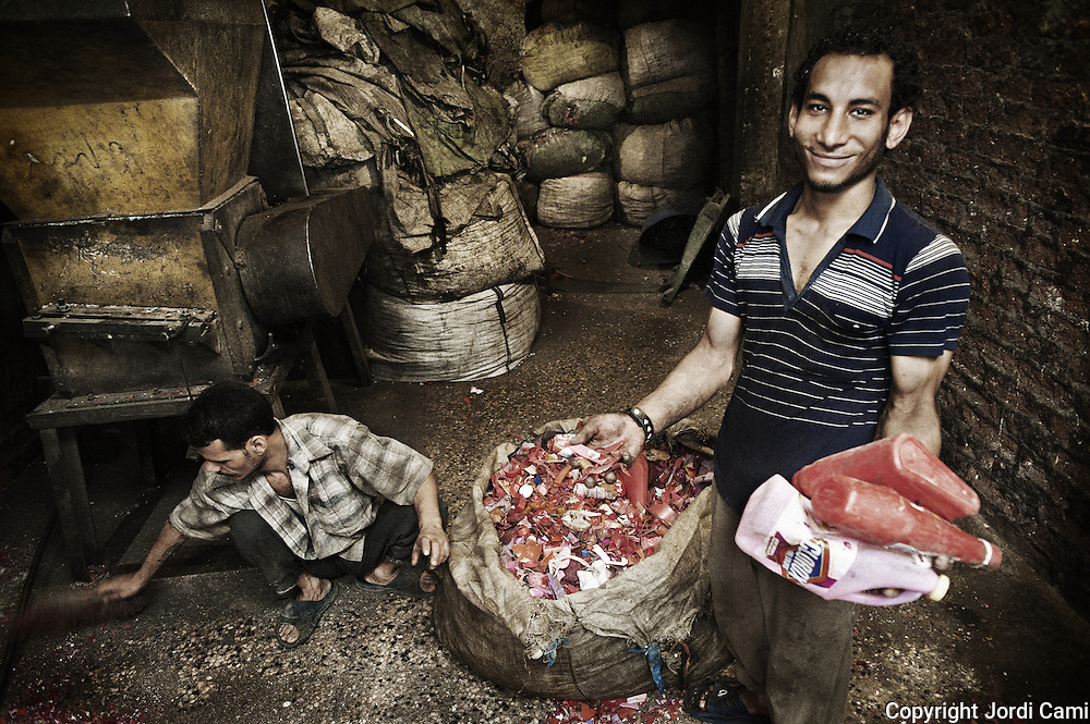 """A young worker """"Zabbeleen"""" at a workshop of Mokattam, shows different types of bottles that are crushed and then will classified by different types of plastic . The quarry was originally located where the settlement of Mokattam, is now used for storage of paper and aluminum. On the outskirts of Cairo in the middle of Manshiet Nasr neighborhood is located Mokattam settlement known as """"Garbage City"""" is inhabited by Zabbaleen, a community of about 45,000 Coptic Christians living for decades to recycle waste generated by the Egyptian capital: plastic, aluminum, paper and organic waste transformed into compost. Most part of the Association for the Protection of the Environment (APE), an NGO that works in the area, whose objectives are to protect the environment and improve the livelihoods of garbage scavengers in Cairo. According to the UN, the work is done in Mokattam is one of the ten best examples of world environmental improvement. El Cairo , Egypt, June 2011. ( Photo by  Jordi Camí )."""