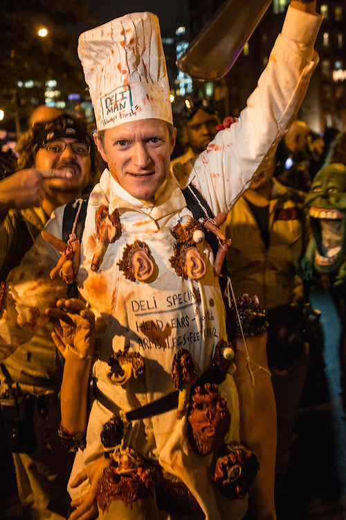 """New York, NY, October 31, 2013. A man in a chef's outfit captioned """"Deli Man"""" and festooned with human body parts in the Greenwich Village Halloween Parade."""