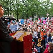 Amsterdam, 21-09-2013.  Vanuit 16 steden in het land kwamen bussen naar Amsterdam met betogers die meededen aan de demonstratie tegen de geplande bezuinigingen van het kabinet. De organisatie Comité Stop Bezuinigingen schatte de opkomst op ongeveer 5000 mensen. De manifestatie begon op het Beursplein. Vandaar trokken de demonstranten naar het beeld van de Dokwerker op het Jonas Daniël Meijerplein. Daar werd gesproken door onder andere SP-leider Emile Roemer en Henk Krol (50Plus). Meer dan 50 maatschappelijke organisaties hebben hun steun toegezegd aan de protestactie. Onder meer de Amsterdamse afdelingen van FNV Bondgenoten, Abvakabo FNV en SP en GroenLinks namen het initiatief tot de demonstratie. Zij menen dat de bevolking ,,het niet langer pikt'' dat de regering weer miljarden wil bezuinigen op onder meer zorg en kinderopvang. Volgens het comité worden de kosten van de crisis afgewenteld op kwetsbare groepen in de samenleving en worden ,,bonussen, belastingontwijking en de topinkomens nauwelijks aangepakt''. Foto Emile Roemer.