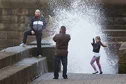 """© Licensed to London News Pictures. 09/11/2015. Bridlington, UK. FRAME 2 OF 9. A man poses for a photograph on the sea defences at the sea side town of Bridlington & gets caught out by a huge wave. The Yorkshire region was hit by severe gales this afternoon with winds up to 60mph. The Met Office warned West Yorkshire to expect gales and locally severe gales over high ground, with some """"very gusty"""" winds to the east of high ground as well.<br /> Photo credit: Andrew McCaren/LNP"""