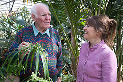 Older man and his carer chatting in a park hot house,