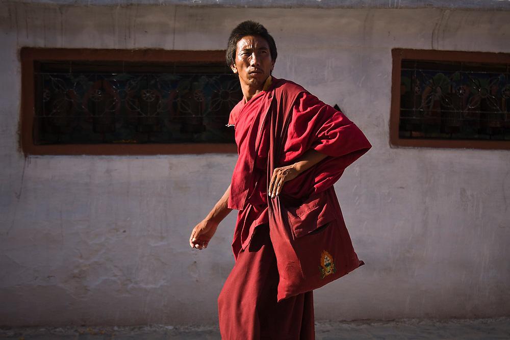 A Buddhist monk walks around the base of Boudhanath Stupa, Kathmandu, Nepal.