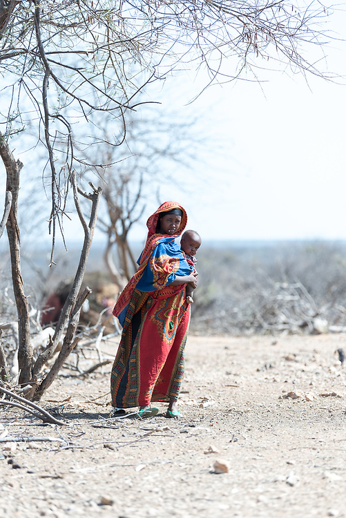 27 January 2019, Burka Dare IDP site, near Micha, Seweyna woreda, Bale Zone, Oromia, Ethiopia: 20-year-old Amina holds her one-year-old child in the shade under a tree in the Burka Dare IDP site. She is on of a group of more than 400 people who arrived here two years ago, as they were driven from their homes in neighbouring Somali. The Lutheran World Federation supports internally displaced people in several regions of Ethiopia, through emergency response on water, sanitation and hygiene (WASH) as well as long-term development and empowerment projects, to help build resilience and adapt communities' lifestyles to a changing climate.