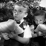 Two ring bearers wait for their turn to go down the aisle during a wedding ceremony at The Governor's Mansion in Columbia, S.C. in this black and white photograph. ©Travis Bell Photography