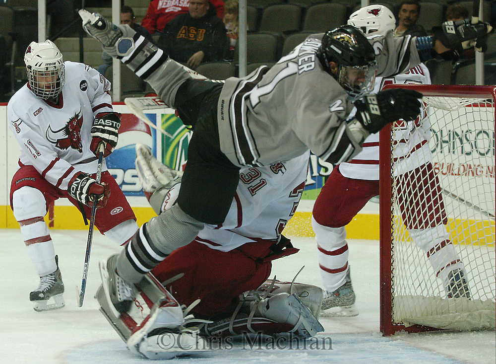 10/23/04 Omaha, Neb. Western Michigan's Pat Dwyer  trips over University of  Nebraska at Omaha goalie Chris Holt while trying to score a short handed goal.  Dwyer was called for a charging penalty giving the Mavs a two-man advantage as University of  Nebraska at Omaha's .Bill Thomas (far left) looks on Saturday night. (chris machian/Prarie Pixel Group)
